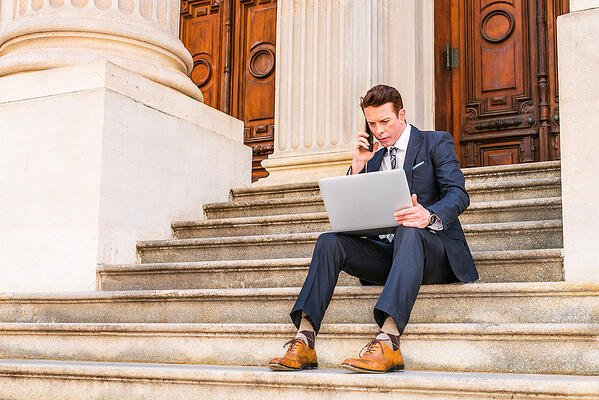 Lawyer works outdoors on laptop