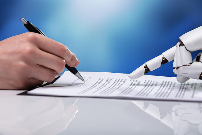 Robot hand points to signature line on a Master Service Agreement for IT services