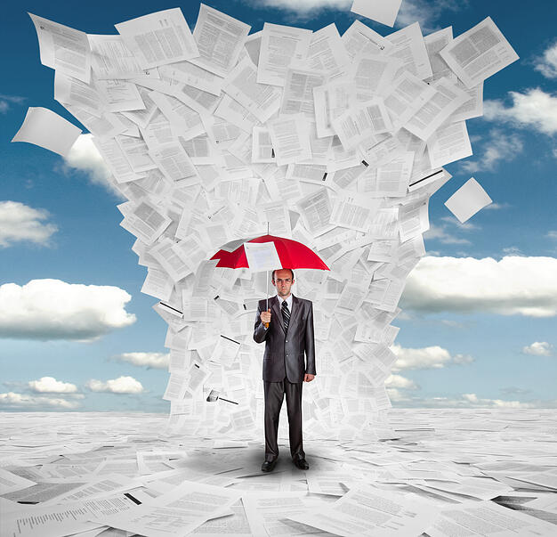 Man holds an umbrella against deluge of documents to illustrate the scope of contract risk management